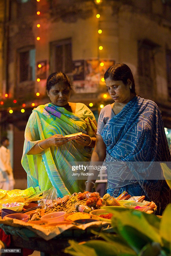 Women buy snacks and spices for their families on the first night of Diwali. During Diwali, the five-day Indian festival of lights, homes are thoroughly cleaned and windows and doors are opened to welcome Laksmi, the goddess of wealth. Mythically, the festival celebrates the victory of the Hindu god Lord Rama over the demon Ravana, and Rama's return to the holy city of Ayodhya..