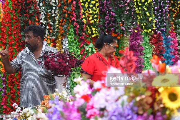 A women buys artificial flowers ahead of Diwali festival at Crowford Market on October 13 2017 in Mumbai India With Diwali just a week away huge rush...