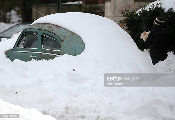 A women carries a dog past an antique car that is buried with snow on January 26 2016 in Washington DC The east coast is still digging out from large...