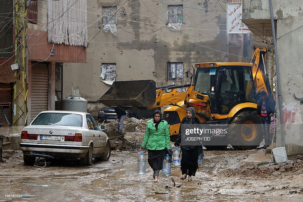 Women carries bottles of water in front of a bulldozer removing garbage, mud and water from the flooded streets in Beirut's southern suburb of Hayy al-Sellum on January 9, 2013 as heavy rains and high speed winds hit Lebanon. A met office official at Beirut airport said the storm would continue and that lower temperatures would result in snowfall in the mountains as low as 300 metres. AFP PHOTO /JOSEPH EID