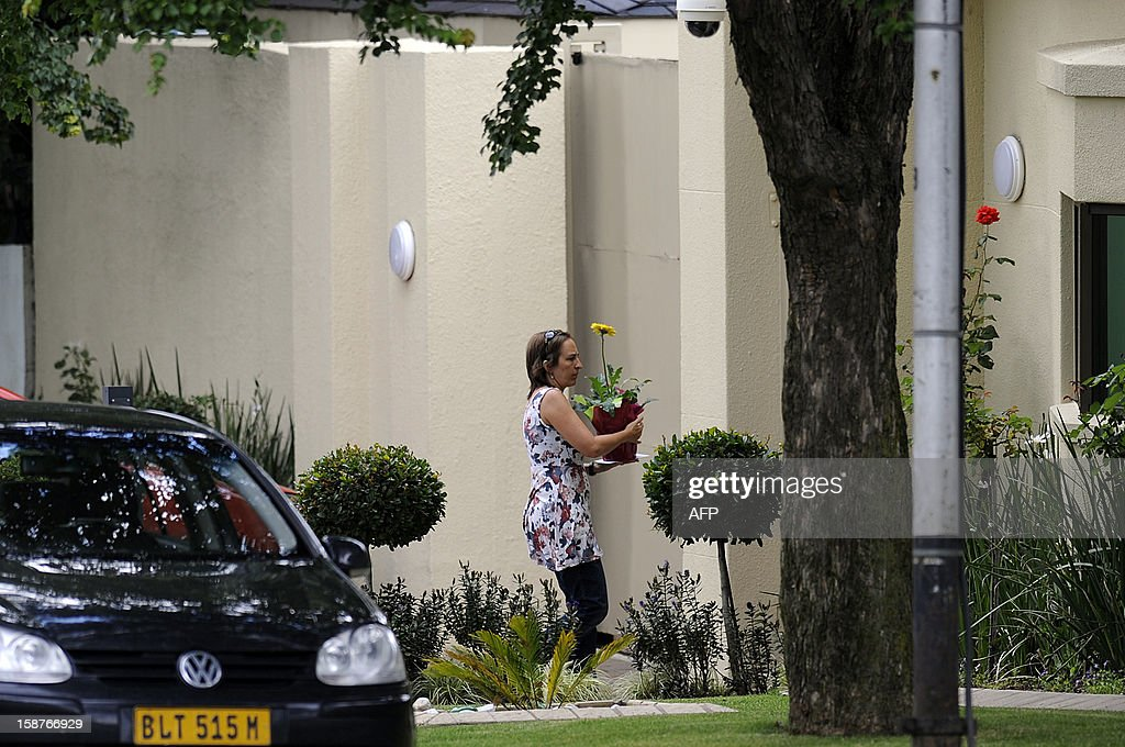 A women carries flowers for Nelson Mandela at his residence in Johannesburg on December 28, 2012. South Africa's anti-apartheid icon Nelson Mandela was recovering at his Johannesburg home today, convalescing and receiving further care after a nearly three-week hospital stay, officials said.