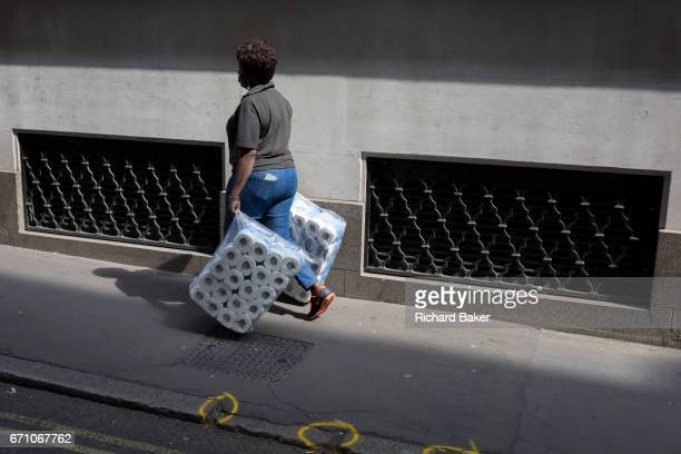 A women carries two large packs of toilet rolls into nearby offices the capital's financial district on 19th April in the City of London England