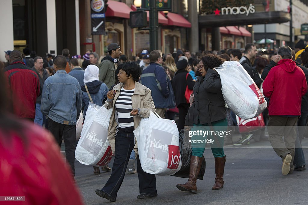 Women carry bags of goods across 34th Street during the Black Friday sales on November 23, 2012 in New York City. Shoppers filled stores in search of the many potential bargains on offer during the traditional yearly sale, which got its name as it's said to put retailers 'in the black,' or making a profit.