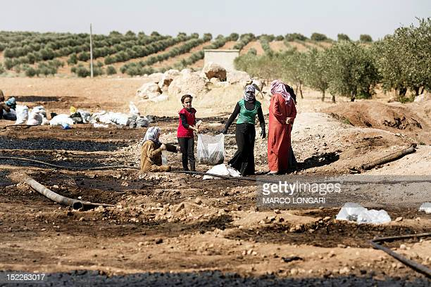 Women carry bags of waste of pressed olives mixed with water before leaving it to dry in the sun in a field near the battled Syrian city of alBab on...