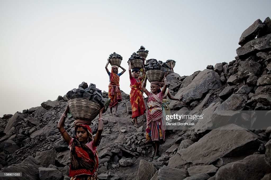 Women carry baskets of coal back to their village for sale, after having scavenged the coal illegally from an open-cast coal mine in the village of Jina Gora on February 09, 2012 near Jharia, India. Villagers in India's Eastern State of Jharkhand scavenge coal illegally from open-cast coal mines to earn a few dollars a day. Claiming that decades old underground burning coal seams threatened the homes of villagers, the government has recently relocated over 2300 families to towns like Belgaria. Villagers claim they were promised schools, hospitals and free utilities for two years, which they have not received. As the world's power needs have increased, so has the total global production of coal, nearly doubling over the last 20 years according to the World Coal Association.