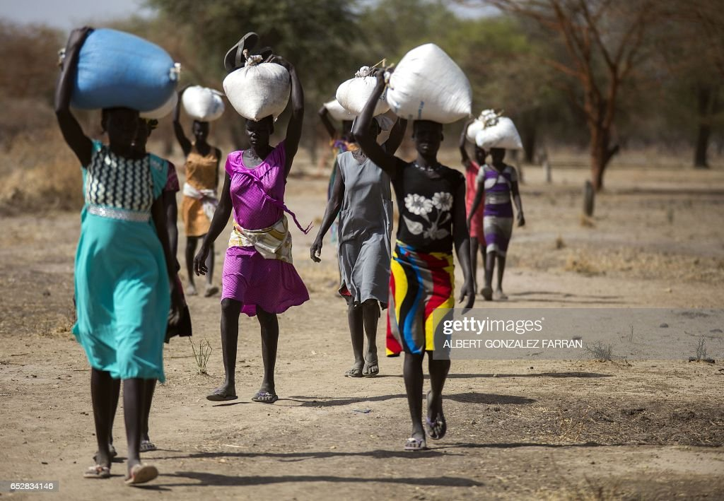 Women carry food in gunny bags after visiting an aid distribution centre in Ngop in South Sudan's Unity State on March 10, 2017. The Norwegian Refugee Council (NRC) distributed food (maize, lentils, oil and corn soya blend) for more than 7,100 people in Ngop. South Sudan, the world's youngest nation formed after splitting from the north in 2011, has declared famine in parts of Unity State, saying 100,000 people face starvation and another million are on the brink of famine. Aid groups have slammed a 'man-made' famine caused by ongoing fighting in the country where civil war has forced people to flee, disrupted agriculture, sent prices soaring, and seen aid agencies blocked from accessing some of the worst-hit areas. /