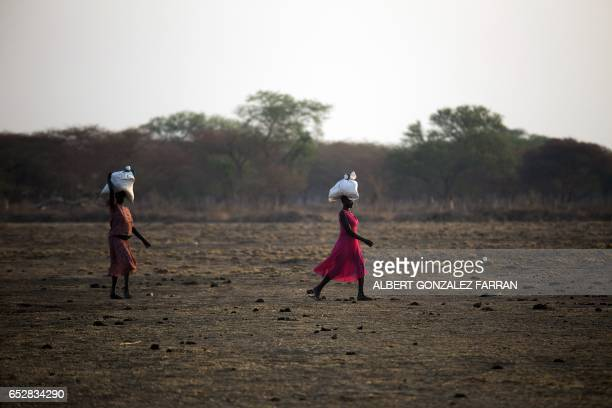 Women carry food in gunny bags after visiting an aid distribution centre in Ngop in South Sudan's Unity State on March 10 2017 The Norwegian Refugee...