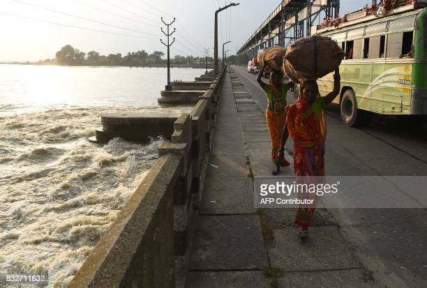 Women carry goods on their heads as they cross Koshi Barrage Birpur Sunsari district some 250 kms from Nepal's capital Kathmandu on August 16 2017 At...