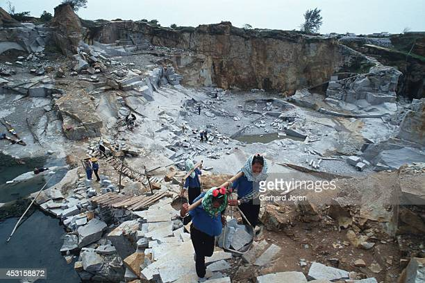 Women carry heavy granite blocks from a quarry near Chong Wu town Hui'An county