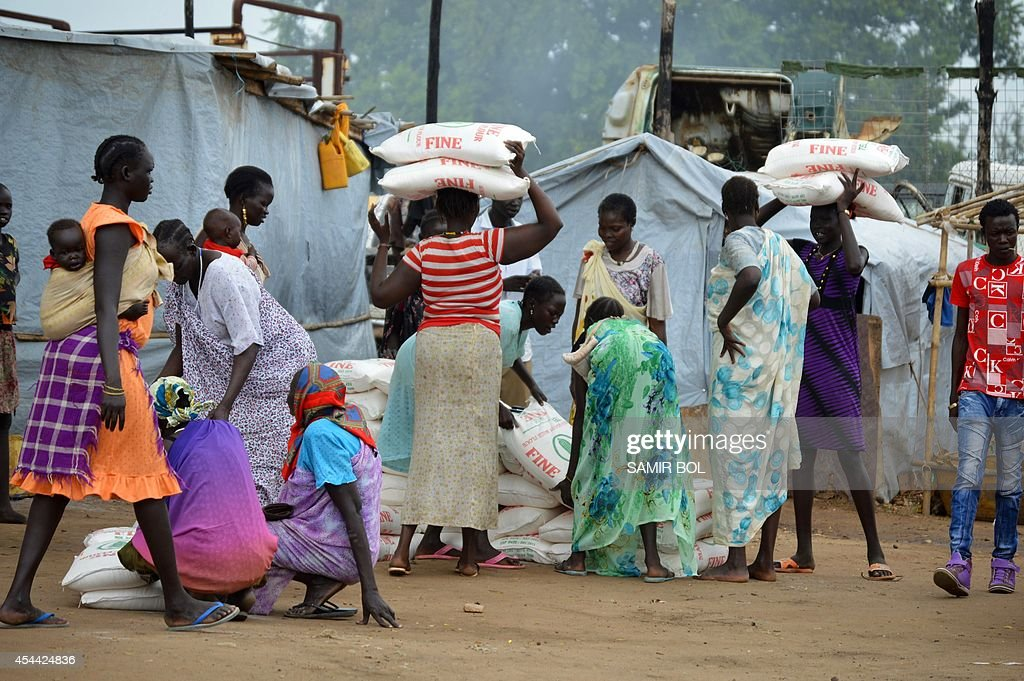 Women carry maize flour sacks during a food distribution by the Catholic Church to refugees and displaced people in Juba on August 30 2014 Wartorn...