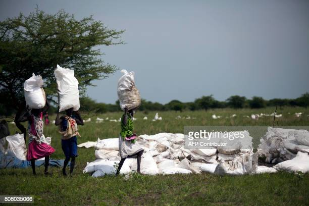 TOPSHOT Women carry sacks of food airdropped by the World Food Programme and distributed by the NGO Oxfam on July 3 2017 in Padding Jonglei South...