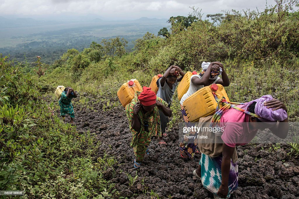 Women carry water to the top of Mount Nyiragongo The Nyiragongo is an active stratovolcano with an elevation of 3470 metres in the Virunga National...