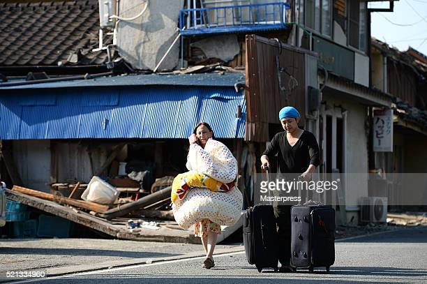 A women carrying a comforter and a man carrying suitcases are seen in front of a collapsed house a day after the 2016 Kumamoto Earthquake on April 15...