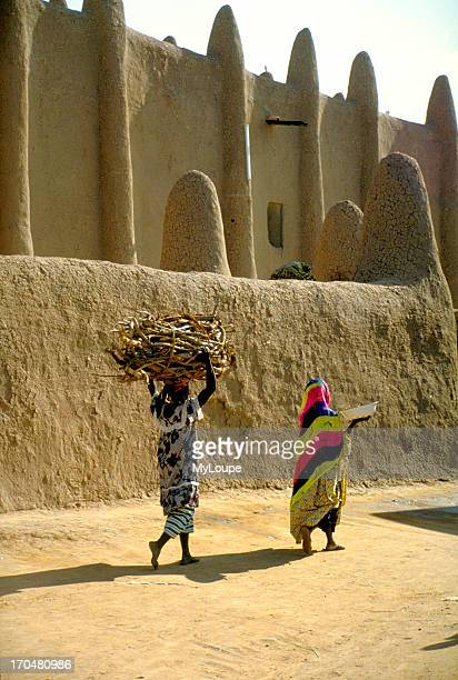 Women carrying firewood near the Great Mosque of Djenne oldest known city in subSaharan Africa on the flood lands of the Niger and Bani rivers 220...