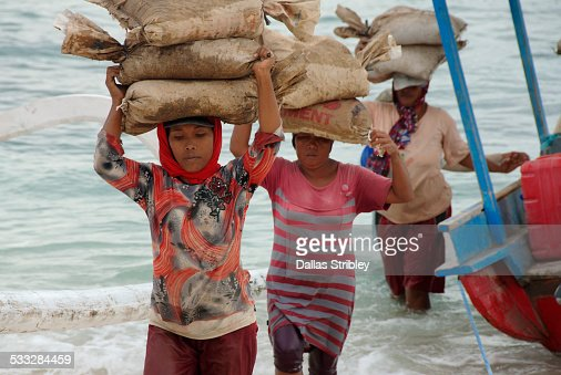 Women carrying heavy sand bags on their heads
