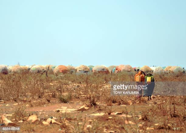 TOPSHOT Women carrying jerrycans of water from a collection point set up by a UN aid agency walk on March 14 2017 towards a makeshift camp on the...