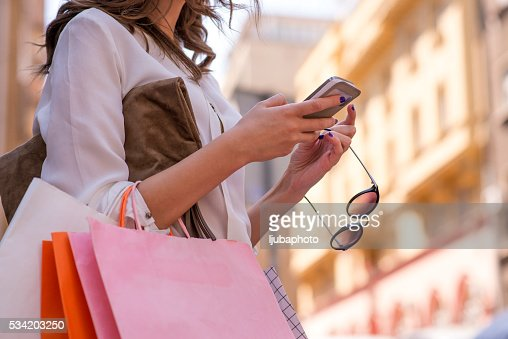 Women carrying shoppings bags and using smartphone