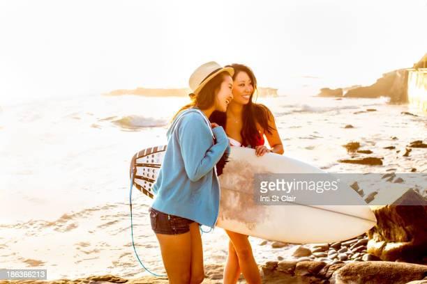 Women carrying surfboard on beach