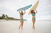 Women carrying surfboards on beach