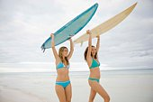 Women carrying surfboards on beach