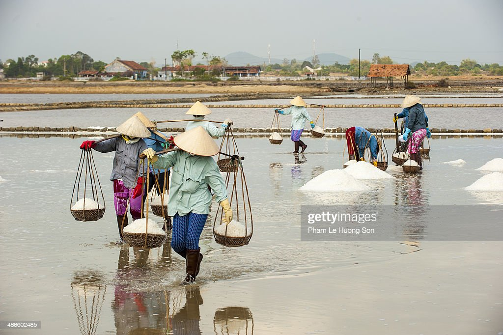 Women carrying the basket full loaded with salt