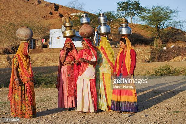 Women carrying water in the traditional way from a well outside of Pushkar, India. (MR)