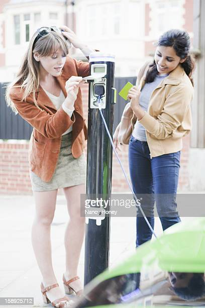 Women charging electric car on street