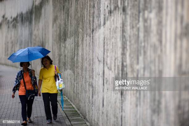Women chat as they walk along a street in a residential area of Hong Kong on April 27 2017 / AFP PHOTO / Anthony WALLACE