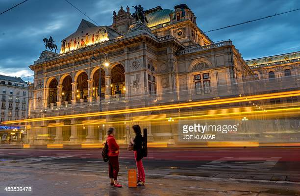A women chat at the tram stop in front of the litup Wiener Staatsoper Vienna's State Opera during the twilight in the city center of Vienna on August...