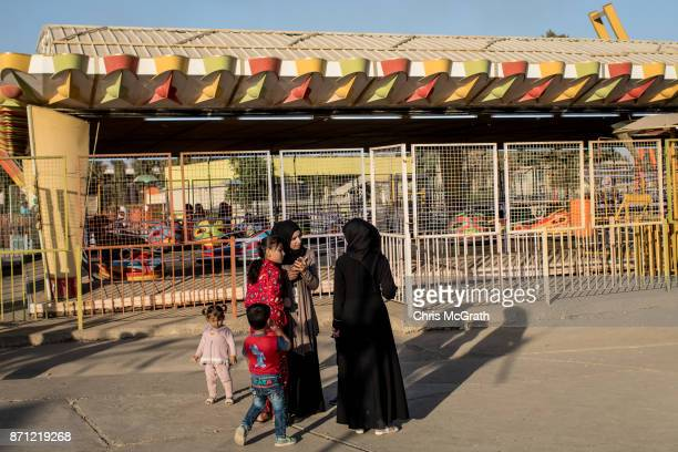 Women chat in front of a ride at the Mosul Amusement Park on November 4 2017 in Mosul Iraq The theme park was shut down under ISIS occupation and the...