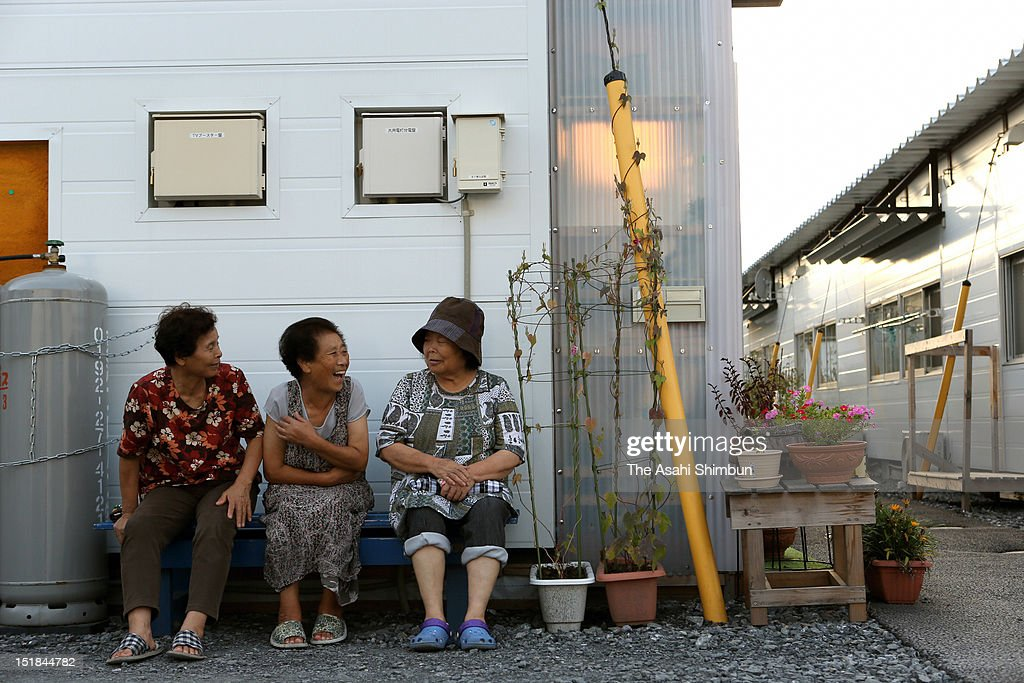 Women chat outside their temporary housing on September 10, 2012 in Ofunato, Iwate, Japan. 18 months on, still 2,814 people are missing and 340,000 people are forced to live at temporary housing.