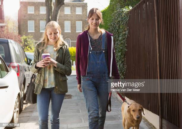 Women chatting and walking with labrador retriever in urban street.