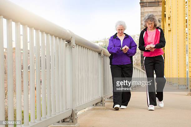 Women Checking Fitness Watches As They Walk