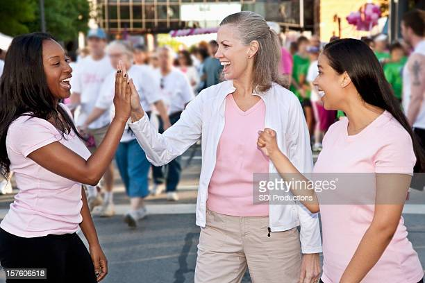 Women Cheering Each Other On at Cancer Awareness Event