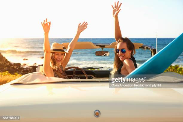 Women cheering in convertible on beach