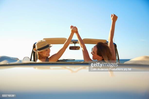 Women cheering in convertible outdoors
