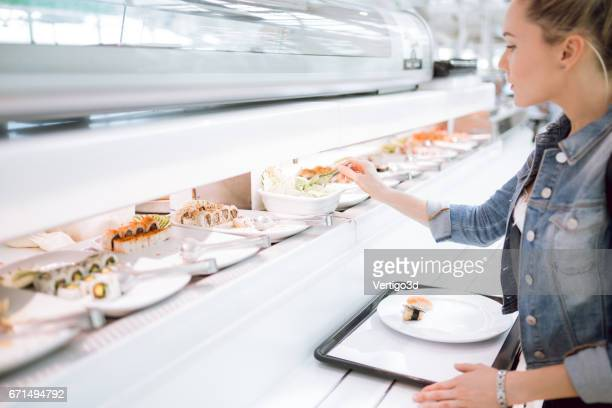 Women choosing sushi on the food court