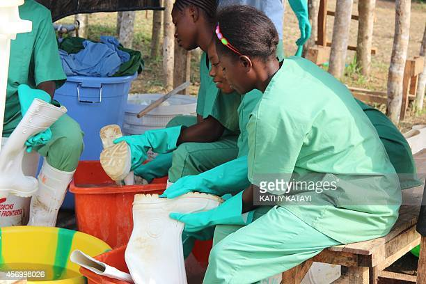 Women clean the clothes of hygienists after their work at the Ebola treatment centre in Lokolia on October 5 2014 AFP PHOTO KATHY KATAYI