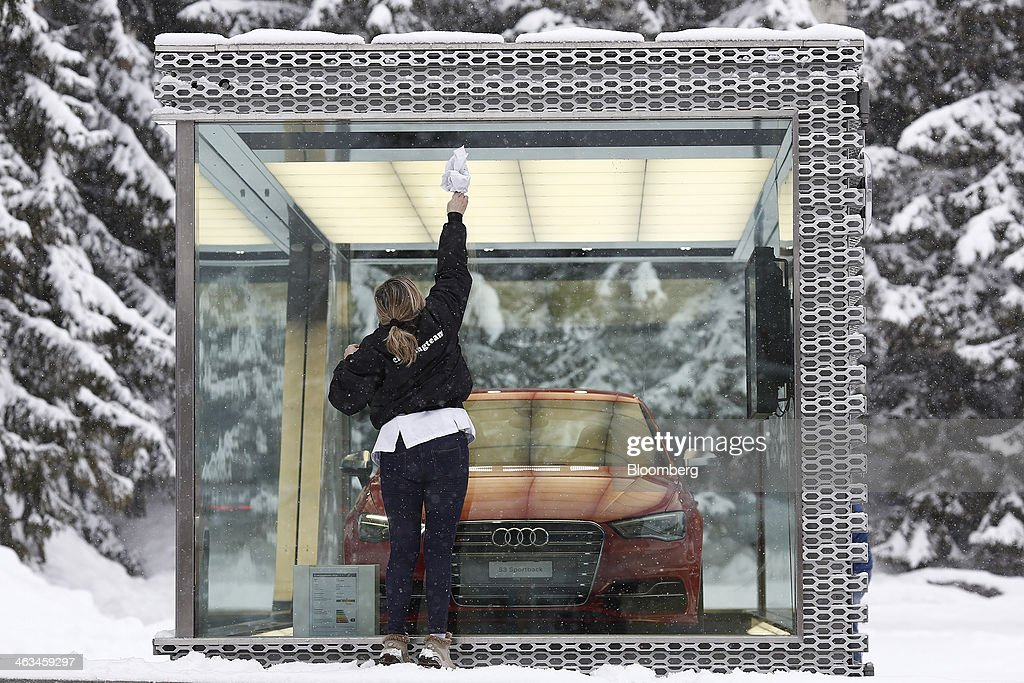 A women cleans a display case for the Audi S3 Sportback automobile, part of a promotion for Audi AG during the WEF week in Davos, Switzerland, on Friday, Jan. 17, 2014. Next week the business elite will gather in the Swiss Alps for the 44th annual meeting of the World Economic Forum (WEF) in Davos for the five day event which runs from Jan. 22-25. Photographer: Simon Dawson/Bloomberg via Getty Images