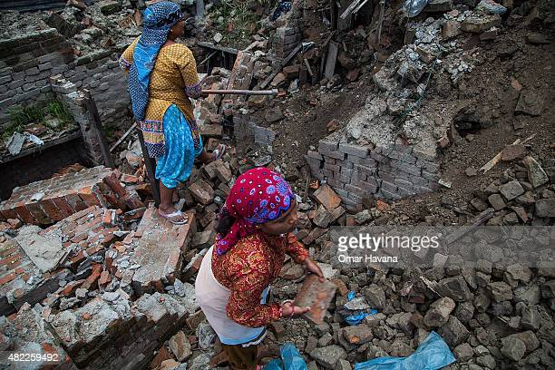 Women clear debris from their collapsed home on July 29 2015 in Bhaktapur Nepal Three months after the earthquake that hit Nepal on April 25th and...