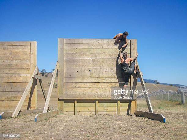Women climbing large wall during obstacle course