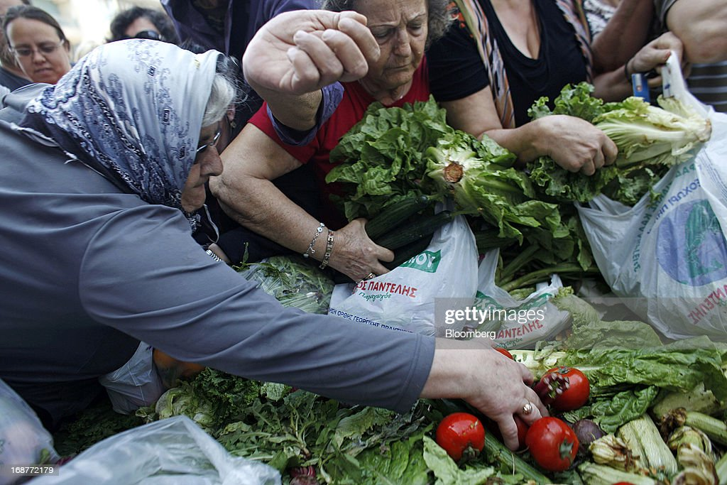 Women collect free vegetables from a stall during a handout of leftover food by striking street vendors in Athens, Greece, on Wednesday, May 15, 2013. Greece's plans to return to international bond markets next year reflect the government's confidence it can draw a line under the country's debt crisis although the cost of borrowing suggests that might be premature. Photographer: Kostas Tsironis/Bloomberg via Getty Images