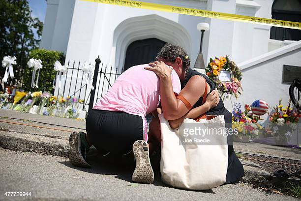 Women comfort each other as they mourn in front of the Emanuel African Methodist Episcopal Church after a mass shooting at the church that killed...