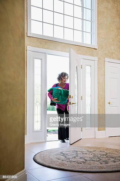 Women coming through front door holding groceries