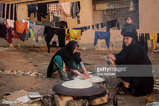 Women cook bread inside the Hassan Sham IDP camp on December 26 2016 in Hassan Sham Iraq In recent weeks the push to liberate Mosul has stalled as...