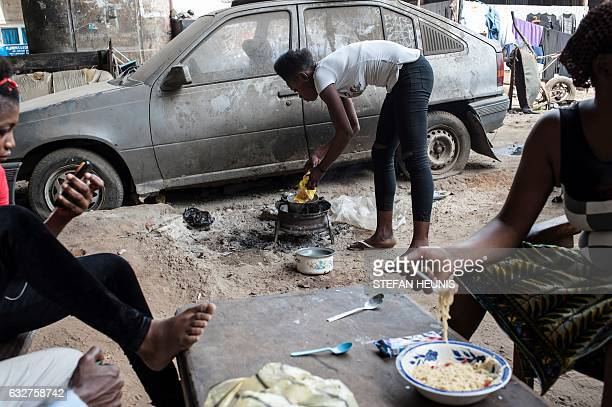 Women cook food under one of the bridges in Lagos on January 6 2017 Nearly two years after taking office Nigeria's President Muhammadu Buhari is...