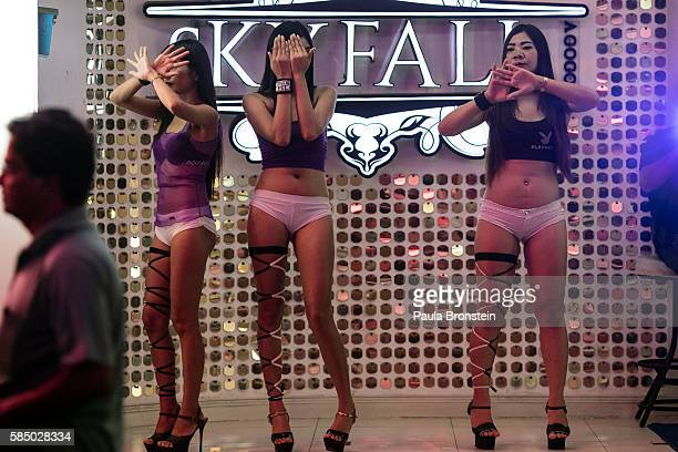 Women cover their faces along the Walking Street where bars and sex scenes are a commonplace July 31 2016 in Pattaya Thailand Thailand's first female...