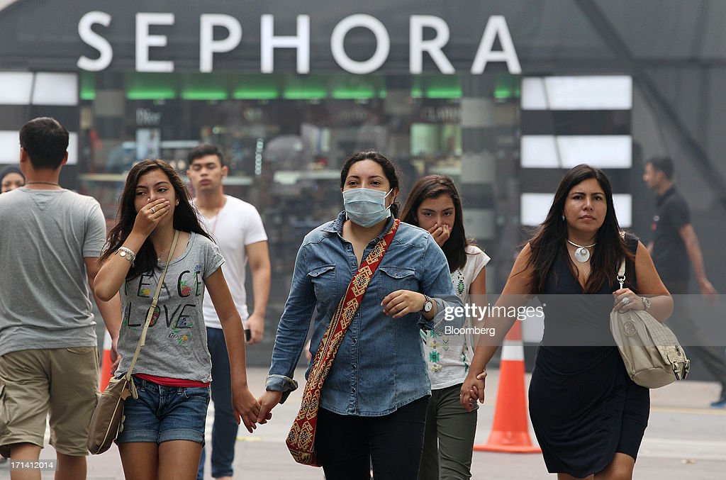 Women cover their faces as they walk along a street past a Sephora SA store in Kuala Lumpur, Malaysia, on Monday, June 24, 2013. Malaysia called for a meeting of Southeast Asian ministers as early as next week after haze from illegal Indonesian forest fires reached hazardous levels in parts of the region. Photographer: Goh Seng Chong/Bloomberg via Getty Images