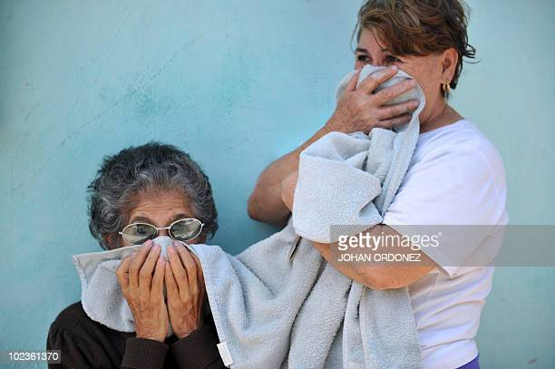 Women cover their faces while a Health Ministry's worker sprays insecticides against the Aedes Aegypti mosquito in a house in Guatemala City on June...