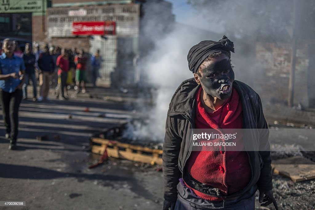A women covered in soot gestures and shouts towards foreign nationals outside the Jeppies Hostles in the Jeppestown area of Johannesburg on April 17...